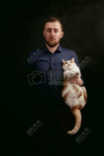 男子灰色衬衫控股白色和橙色毛皮猫