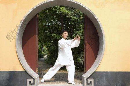 拱形门前打太极拳的中年师傅图片图片